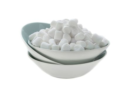 Bowl of white miniature marshmallows isolated against a white background.