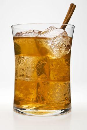 chai: Chai Tea Cocktail against a white background with a cinnamon stick as a garnish. Stock Photo