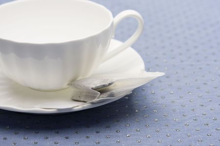 Empty white china tea cup and saucer with tea bag laying on top of a glitter blue tabletop. photo