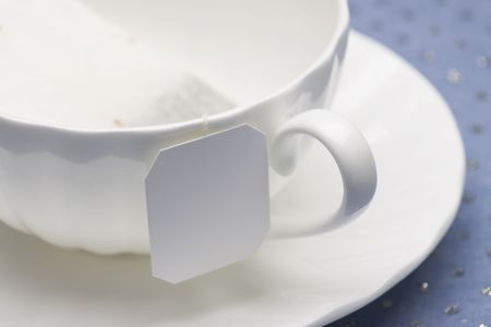 Empty white china tea cup and saucer with tea bag laying on top of a glitter blue tabletop.