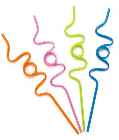 Orange, pink, lime and blue colorful curly drinking straws against a white background.