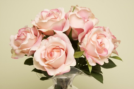 Bouquet of pink roses in a glass vase against a light green background.