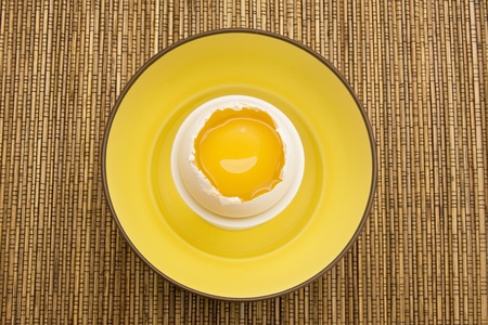 Raw egg cracked open with yellow yolk inside a white eggshell in a yellow bowl on top of a bamboo placemat. photo