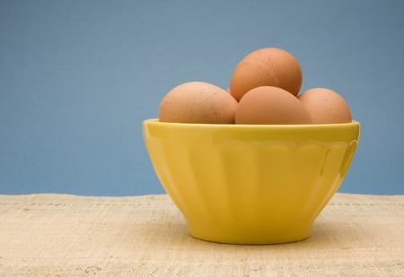 Bowl of uncooked brown eggs in a yellow bowl.