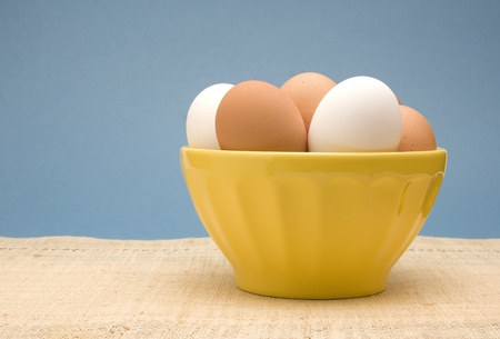 Bowl of uncooked white and brown eggs in a yellow bowl. photo