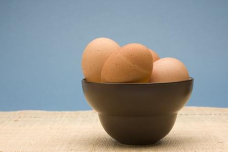 갈색 그릇에 생 쌀된 갈색 계란의 그릇입니다.