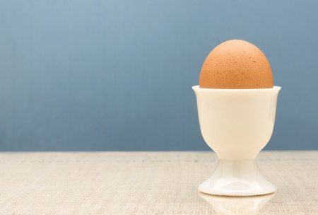 Fresh brown egg placed in a white eggcup.