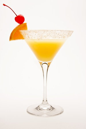 Desert Sand Tequila Sunrise Cocktail against a white background garnished with a cherry and orange wedge. photo