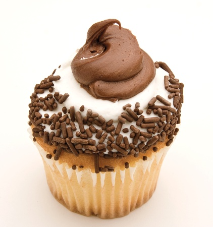 Yellow cupcake covered in chocolate icing and sprinkles against a white background.
