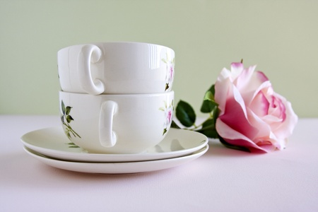A pair of china teacups and a single pink rose flower.