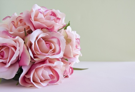 Bouquet of pink roses laying on a table.
