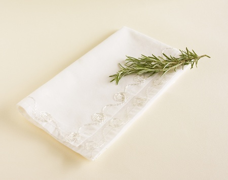 Sprig of fresh rosemary laying on top of a white napkin.