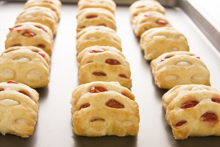 cookie sheet: Strawberry strudel bites in rolls on a cookie sheet.