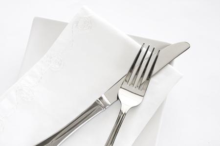 Bestecke Einstellung einer Gabel, Messer und weiße Serviette auf einem weißen Teller vor einem weißen Hintergrund. Standard-Bild