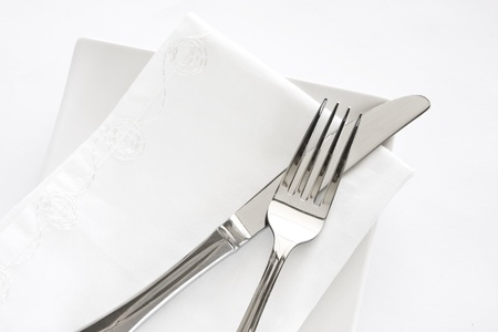 napkin: Flatware setting of a fork, knife and white napkin on a white plate against a white background.