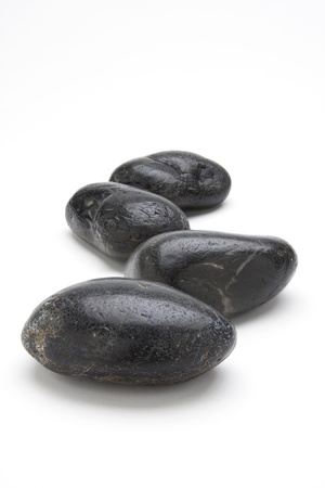 river rock: Black river rocks used in spa treatments against a white background. Stock Photo