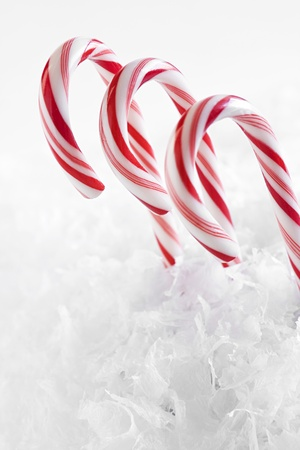 Red and white candy canes surrounded by faux snowflakes against a white background. Stock Photo - 11890636