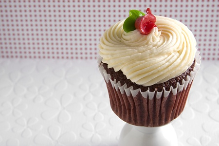 Red velvet cupcake with butter cream frosting against a red and white polka dot background. photo
