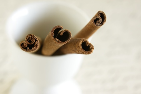 Close up view of a pile of cinnamon sticks in a white egg cup. Imagens