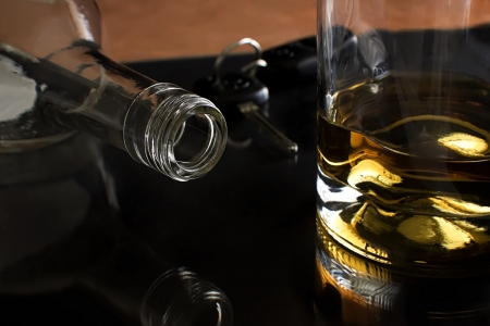 Bottle of liquor laying on its side, glass of liquor and car keys in the background. Stock Photo