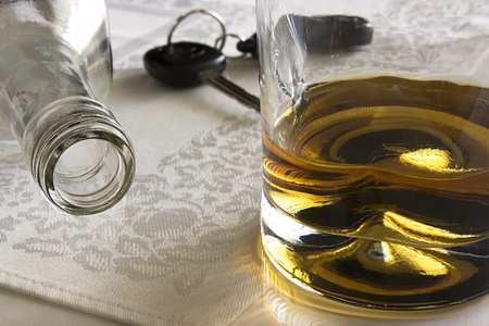Bottle of liquor laying on its side, glass of liquor and car keys in the background. photo