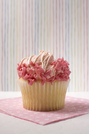 Yellow cupcake decorated with pink icing against a multi-colored striped background. Stock Photo - 12251173