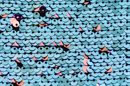 Sequins macro background. Multicolored sequins. Paillette fabric background. Sparkling sequined textile. Selective focus.