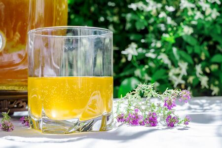 Refreshing kombucha tea with thyme in a glass on backdrop of blurred flowers. Healthy natural probiotic flavored drink. Copy space.