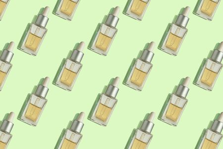 Seamless pattern of anti aging serum in glass bottle with dropper on pastel mint background. Creative layout, cosmetic seamless pattern, flat lay. For packaging design, printing on fabric, paper