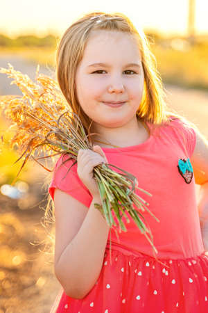 Cute smiling little girl in pink dress with bouquet of dried flowers in her arm outdor in sunset. Activities with children summer outdoors. Vertical. Imagens