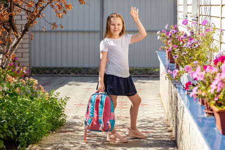 Back to school concept. The child goes to school. Cute little girl outside in the morning, goes to school and waving to mom goodbye. Standard-Bild