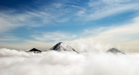 view from the above: peaks of mountains above the clouds, Russia, Kamchatka Stock Photo