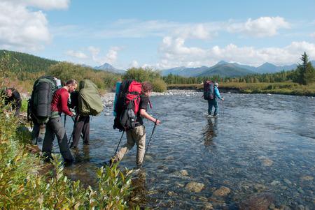 hikers crossing mountain river, Ural, Russia Standard-Bild