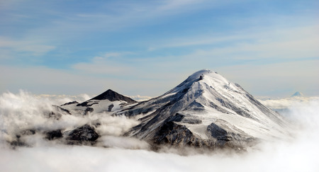above: peaks of mountains above the clouds, Russia, Kamchatka Stock Photo