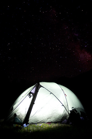 night camping with starry sky and highlighted tent Standard-Bild
