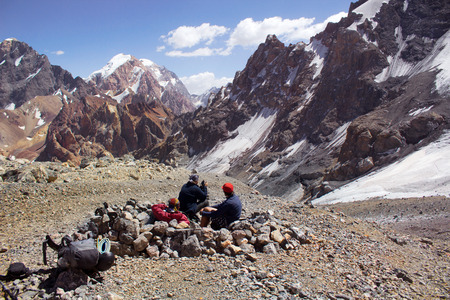 three hikers relaxing after hard rush, Fann Mountains, Tajikistan, central Asia