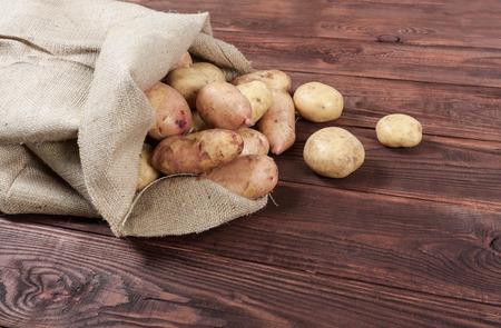 木製の背景の黄麻布の袋でジャガイモを収穫します。 写真素材