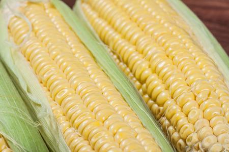 Ripe corn on wooden background. Macro