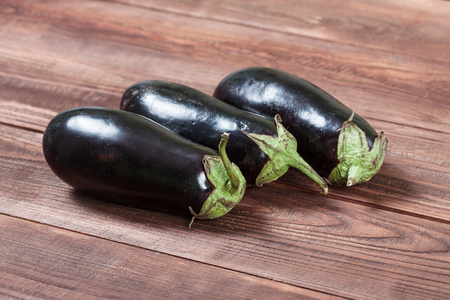 three eggplants on a wooden background
