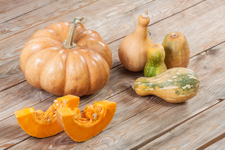 large and small pumpkins on wooden background