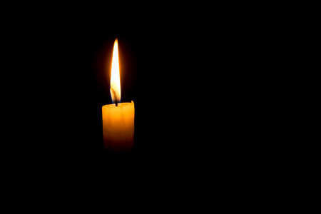 Yellow single candle on a dark black background Standard-Bild
