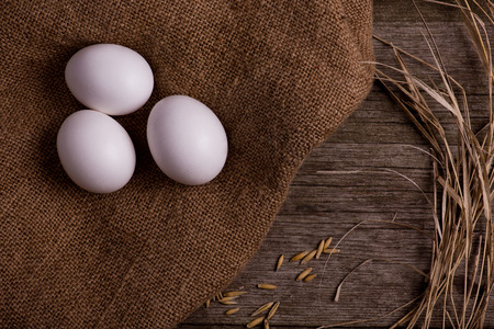 chicken organic eggs with straw on burlap background