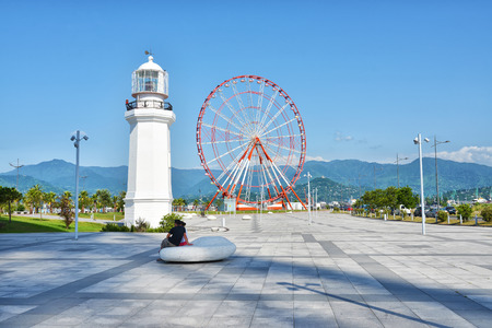 promenade: Georgia Batumi Ferris Wheel and white lighthouse Black Sea coast