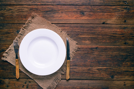 books on a wooden surface: empty white plate with old fork and knife on rustic wooden background