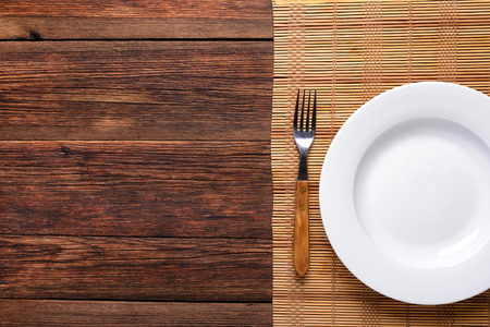 empty white plate with old fork on rustic wooden background Standard-Bild
