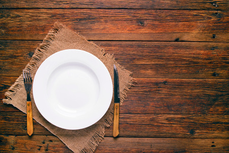 empty white plate with old fork and knife on rustic wooden background