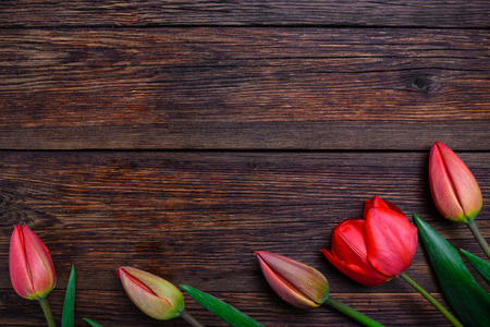 fire flower: Red tulips flowers bouquet on old wooden table background. Top view with copy space.