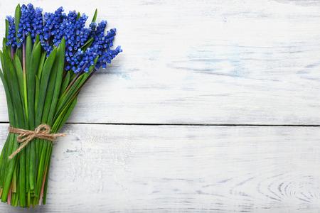 blauwe Muscari lentebloemen boeket op houten tafel. Bovenaanzicht, kopieer ruimte. Stockfoto