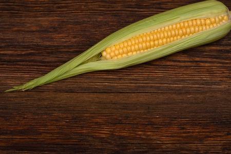 closeup view: Fresh corn on the wooden table closeup, top view horizontal