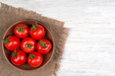 tomatoes on wooden table in bowl top view copy space
